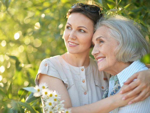 Happy senior mother and adult daughter posing together outdoors