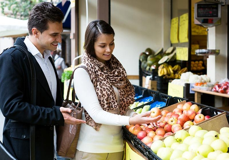 Young happy spouses choosing sweet fruits in grocery outdoors